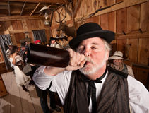 Drunken Man in Bar. Drunken men chugs a bottle of alcohol in a saloon stock photos