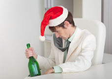 Drunken man in Christmas cap with bottle in a hand Stock Photos