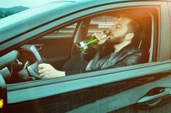 A drunken man driving a car with a bottle of alcohol in his hand.A Man drinking beer at the wheel of a car. A drunken man driving a car with a bottle of alcohol royalty free stock photos