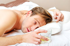 Drunken man lying on bed with glass of whisky Royalty Free Stock Photography