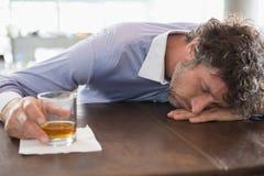 Drunken man sleeping on a bar counter Royalty Free Stock Image