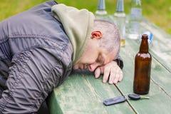 Drunken men near bottles of alcohol at outdoor Stock Image