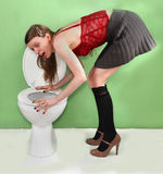 Drunken night. Young woman leaning to vomit over toilet after drunken night out Royalty Free Stock Image