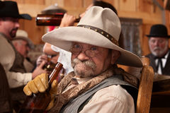 Drunken Old Cowboy. Old cowboy holding whiskey bottle in a saloon Stock Photography
