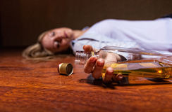 Stop alcohol!. Drunken young woman lying on the floor. Focus on the bottle Royalty Free Stock Photo
