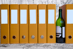 Drunkenness on the working place. Bottle of wine between yellow data folders. Hard drinking on the jobsite Stock Images