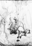 Druppeltjes die van zwarte inkt in water dalen Royalty-vrije Stock Foto