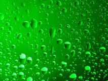 Druppeltjes van water op een warme groene achtergrond Stock Afbeelding