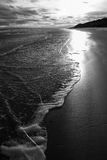 Druridge Bay Shoreline at Incoming Tide. White frothy waves lap onto the silky sand shore as the sun lowers and lights up the incoming tide. Druridge Bay Stock Images