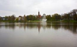 Druskonismeer met een fontein en een mening van de waterkant Stock Fotografie