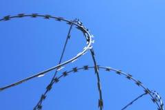 Drut kolczasty na ogrodzeniu z niebieskim niebem poj?cie wi?zienie, salwowanie, kopii przestrze? zdjęcia royalty free