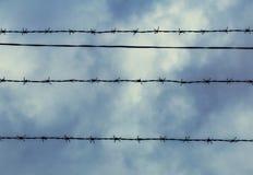Drut kolczasty przeciw niebieskiemu niebu z białymi chmurami Z przestrzeni? dla teksta obrazy stock