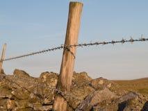 Drutu kolczastego ogrodzenie na kamiennej ścianie Fotografia Stock