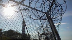 Drutu kolczastego ogrodzenie pod słońce ostrością wewnątrz out Lato więzienie Latarni morskiej tło