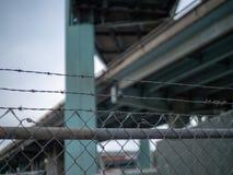 Drutu kolczastego płotowy obsiadanie pod autostrada wiaduktem zdjęcie stock