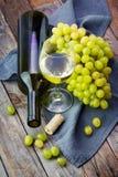 Druva, en flaska och exponeringsglas av vitt vin med druvan på träflik Arkivfoto