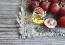 Druvan kärnar ur olja i en glass krus och nya druvor på den gamla trätabellen Flaskan av den organiska druvan kärnar ur olja för  royaltyfri foto