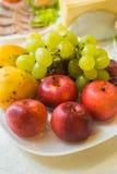 Druvor, äpplen och päron på en platta royaltyfria foton