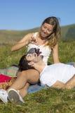 Druvor i flickor räcker matning hennes pojkvännolla av en picknick fotografering för bildbyråer