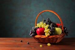 Druvor och äpplen i en vide- korg Arkivfoton