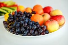 Druvor och äpplen på en vit platta royaltyfria foton