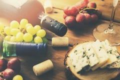 Druvor och ost för vinflaskor på den gamla trätabellen royaltyfri fotografi