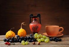 Druvor och pumpor med den keramiska tillbringaren Fotografering för Bildbyråer