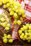 Druvorna i vinexponeringsglaset och i korgen på trätabellen Royaltyfri Foto