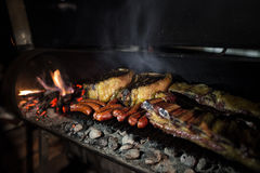 Dry aged meat. Bbq - asado - with dry aged meat, chorizos, cow ribs and cauliflower cooked in a argentina style chulengo grill royalty free stock photo