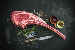 Dry aged raw tomahawk beef steak. With ingredients for grilling royalty free stock photography