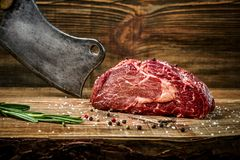 Dry aged Ribeye Steak with seasoning on wooden background. Still life. Copy space. Close-up Stock Photo