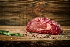 Dry aged Ribeye Steak with seasoning on wooden background. Still life. Copy space. Close-up Royalty Free Stock Photography