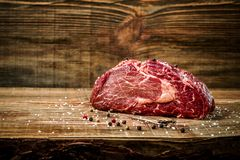 Dry aged Ribeye Steak with seasoning on wooden background. Still life. Copy space. Close-up Royalty Free Stock Image