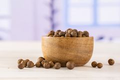 Dry allspice berries with blue window. Lot of whole dry brown allspice berries with wooden bowl with blue window in background royalty free stock images
