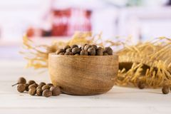 Dry allspice berries with kitchen behind. Lot of whole dry brown allspice berries with wooden bowl on jute cloth with grey kitchen in background stock photo