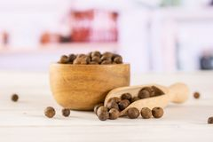 Dry allspice berries with kitchen behind. Lot of whole dry brown allspice berries with wooden bowl and wooden scoop with grey kitchen in background stock images