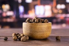 Dry allspice berries with restaurant. Lot of whole dry brown allspice berries with wooden bowl with restaurant in background royalty free stock photo