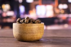 Dry allspice berries with restaurant. Lot of whole dry brown allspice berries with wooden bowl with restaurant in background royalty free stock image