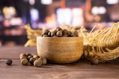 Dry allspice berries with restaurant. Lot of whole dry brown allspice berries with wooden bowl on jute cloth with restaurant in background stock photography