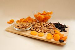 Dry apricots, nuts  and dry black grapes on a wooden dostochka - it is tasty and beautiful, fruit a still life fruit still life. Dry apricots, nuts and dry black Royalty Free Stock Images