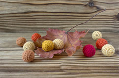 Dry autumn maple leaf on wooden background. Herbarium. Artistic original backdrop. Handmade crochet beads, knitting, sewing, homem Royalty Free Stock Image