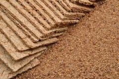 Dry bantar knapriga bröd och väsentligt vetemjöl på träbackgro royaltyfria bilder
