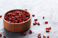 Dry barberries. Pile of dry barberries in bowl on grey wooden table Royalty Free Stock Images