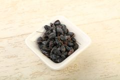 Dry barberry. In the bowl over wooden background stock image