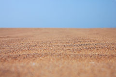 Dry beach sand and clear blue sky Royalty Free Stock Images