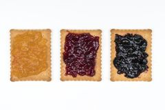 Dry biscuits. Some dry biscuits with jam on a white surface Royalty Free Stock Photography