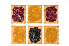Dry biscuits. Some dry biscuits with jam on a white surface Royalty Free Stock Photo