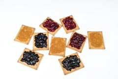 Dry biscuits. Some dry biscuits with jam on a white surface Royalty Free Stock Photos