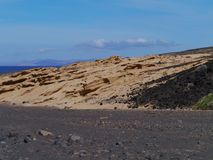 The dry black river bedding on the Jandia Peninsula. The yellow limestone dunes along the black river bedding in the Jandia nature park on the Canary Island Royalty Free Stock Photos