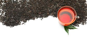 Dry black tea leaves and cup of aromatic beverage on white background stock images